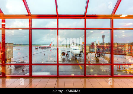 View from the red checkered airport window to the morning airfield with airplanes - Stock Photo