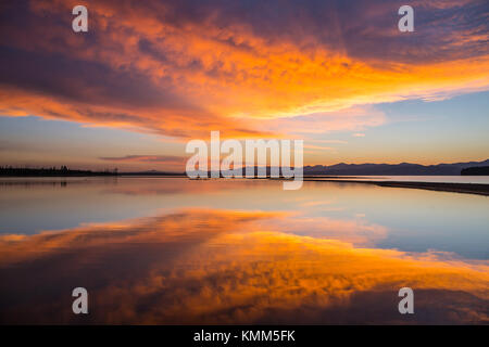 The sunrise reflects off of the Flat Mountain Arm of Yellowstone Lake at the Yellowstone National Park August 7, - Stock Photo
