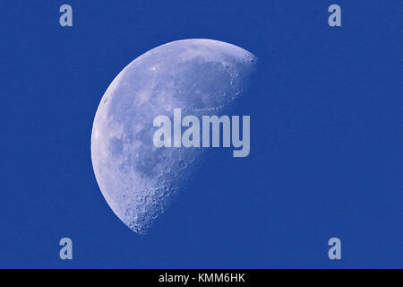 waxing moon in its first quarter in early morning daylight in Italy in early November northern hemisphere - Stock Photo