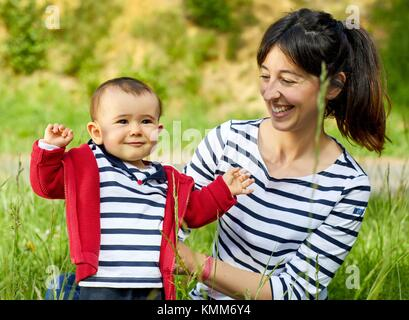 Mother and baby in the park, Getaria, Gipuzkoa, Basque Country, Spain - Stock Photo