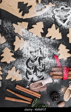 Frame of baking ingredients and tolls for gingerbread. Cookies and spices over rustic table with Christmas tree - Stock Photo