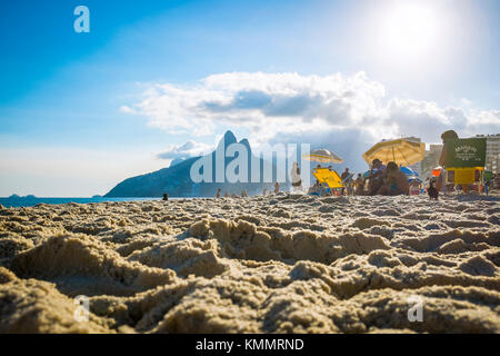 RIO DE JANEIRO - MARCH 06, 2016: People relax on Ipanema Beach against the iconic silhouette of Two Brothers Mountain - Stock Photo