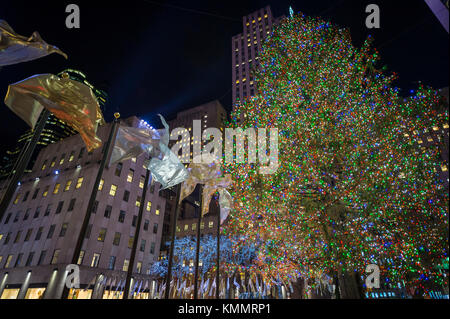 Holiday flags fly around the central plaza in front of the Rockefeller Center Christmas Tree, one of New York City's top winter tourist attractions