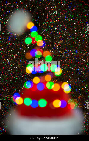 Colorful defocused holiday lights glowing on a Santa hat in front of a twinkling Christmas tree background - Stock Photo