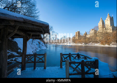 Bright morning view of a scenic gazebo on the edge of the frozen lake in Central Park after a winter storm covered - Stock Photo
