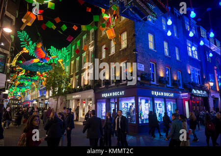 LONDON - NOVEMBER 21, 2017: Shoppers crowd Carnaby Street, a pedestrianised retail zone in the West End, decorated - Stock Photo