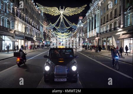 LONDON - NOVEMBER 21, 2017: A black cab waits under twinkling Christmas angels lighting up the upscale shopping - Stock Photo