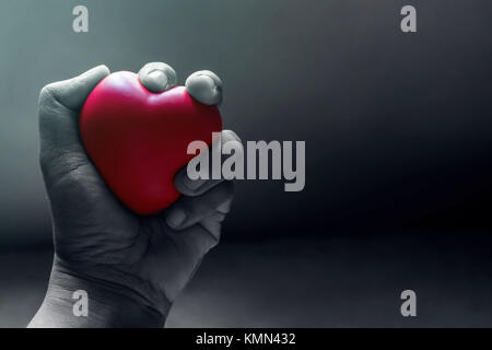 Love and Pain Concept, Hand Squeezing a Red Heart with Anger and Suffering in the Dark Light Room - Stock Photo