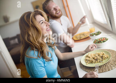 Couple having breakfast in the morning and smiling - Stock Photo