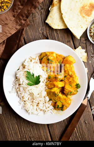 Chicken curry with rice on wooden background. Top view, flat lay - Stock Photo