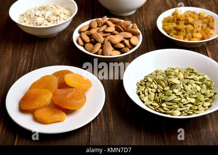 Healthy snack in bowl. Ingredients for cooking granola on wooden table. - Stock Photo
