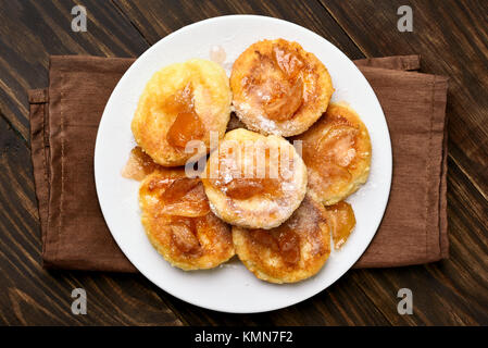 Curd cheese pancakes with caramelized apple slices on wooden table. Top view, flat lay - Stock Photo