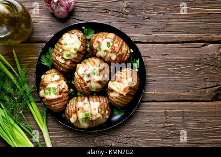 Cooked baked potatoes with bacon, green onion and cheese on wooden background with copy space. Top view, flat lay - Stock Photo