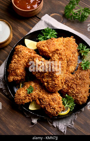 Crispy chicken wings. Dish for dinner on black plate - Stock Photo