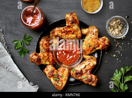 Fried chicken wings with sauce on dark background. Top view, flat lay - Stock Photo
