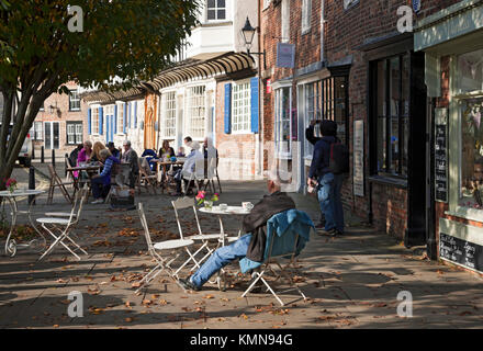 People sitting at outdoor pavement cafe tables in the city centre York North Yorkshire England UK United Kingdom - Stock Photo
