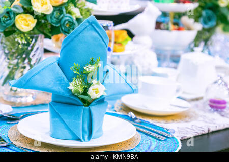 party table setting with a blue napkin, flower, white plate and white teacup in the celebration day. decoration - Stock Photo