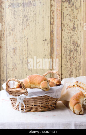 Fresh homemade baked bagels in basket and on baking paper over light gray tablecloth - Stock Photo