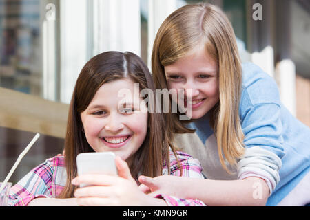 Two Young Girls At Cafe Reading Text Message On Mobile Phone - Stock Photo