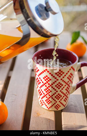 Pouring tangerine tea into cup on wooden table - Stock Photo