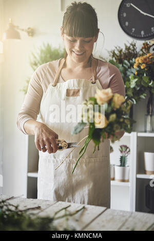 Smiling young female florist standing at a table in her flower shop trimming stems while making a bouquet of mixed - Stock Photo