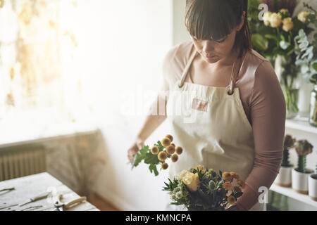 Young female florist working alone at a table in her flower shop making a mixed flower arrangement - Stock Photo