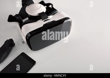 Black and white virtual reality glasses with smartphone on white metraquilate table and white isolated background. - Stock Photo