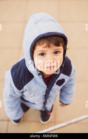 little boy with raincoat hood looking at camera for portrait outdoors - Stock Photo
