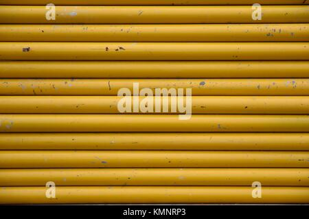 Wall of stacked of weathered worn yellow steel metal pipes, horizontal patterns, full frame