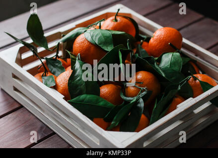 Wooden box of fresh tangerines with leaves - Stock Photo