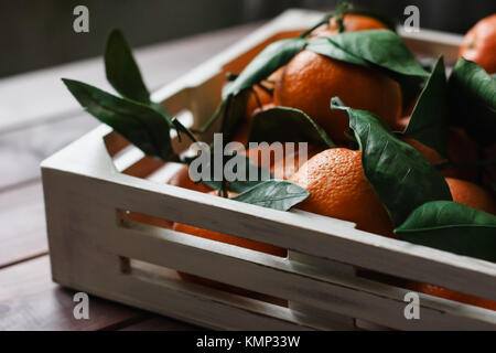 Wooden box of fresh tangerines with leaves on table - Stock Photo