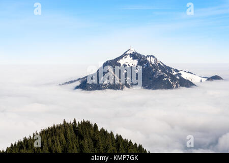 Mountain stick out of foggy cloud layer. Gruenten, Bavaria, Germany. Foresight and vision for business concept and - Stock Photo