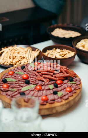 Vertical shot of different appetizers on the wedding table set. The dishes are full of various sausages and chips. - Stock Photo