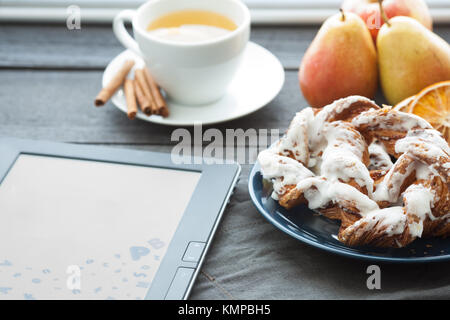 E-book and Bavarian cream puff with crushed hazelnut and lemon fudge on a blue plate. In the background is a cup - Stock Photo