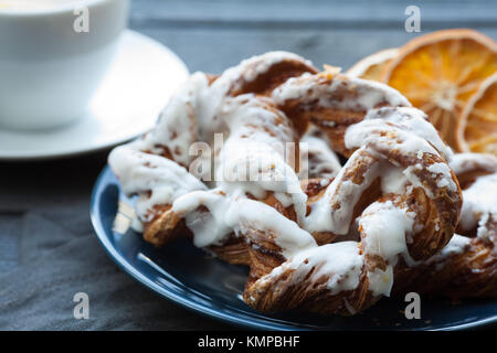 Bavarian cream puff with crushed hazelnut and lemon fondant on a blue plate. In the background a cup of tea and - Stock Photo