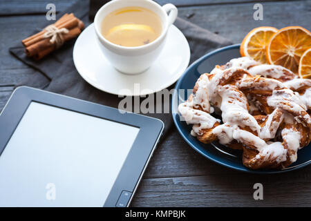 E-book and Bavarian cream puff with crushed hazelnut and lemon fudge on a blue plate. In the background a cup of - Stock Photo