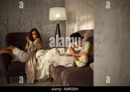 Young woman in a peignoir and her little daughter in dress and black hat are resting on sofa in room. - Stock Photo