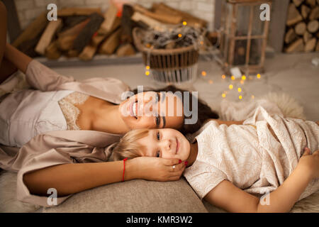 Happy mother in peignoir with her little daughter lies on floor and smiles. Side view. - Stock Photo