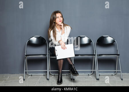 Portrait of confident serious young European female sitting on chair in waiting room with blank, setting her mind - Stock Photo