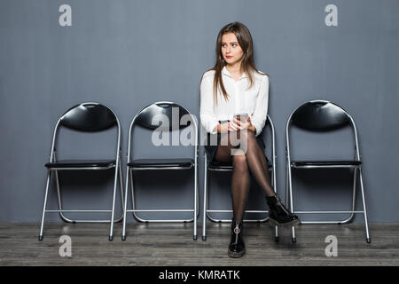 Charming happy young unemployed woman in glasses smiling y having confident look before job interview, sitting on - Stock Photo