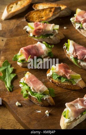 Homemade Prosciutto Pear Cheese Crostini with Arugula - Stock Photo