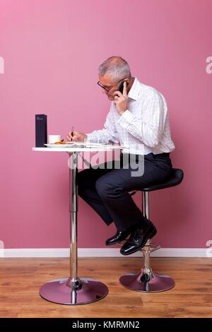 Businessman in smart casual attire sat on a bar stool in a cafe working through his lunch break - Stock Photo
