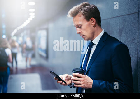 Young businessman drinking coffee and reading text messages on his cellphone while standing on a subway platform - Stock Photo
