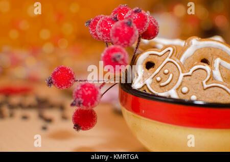 Christmas gingerbreads with white frosting in a colorful bowl, coffee beans and rowan twig for decoration on a wooden - Stock Photo