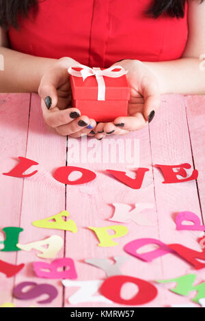 Woman Hands Holding A Red Gift Box Over Pink Wooden Table Full Of Multicolor