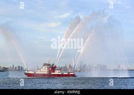Fire Fighter II fireboat with waterjets at full power in front of Lower Manhattan (including One World Trade Center) - Stock Photo