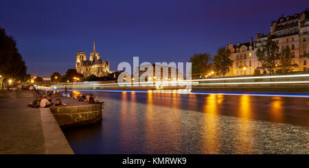 Summer evening on the Seine River banks with Notre Dame de Paris cathedral illuminated. Ile de La Cite and Ile Saint - Stock Photo