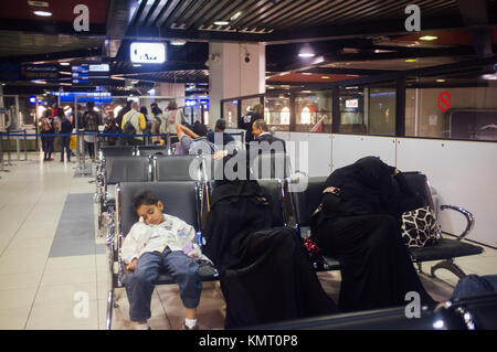 Muslin little boy sitting along with her fully clothly covered women parents. Tel Aviv, Israel. - Stock Photo