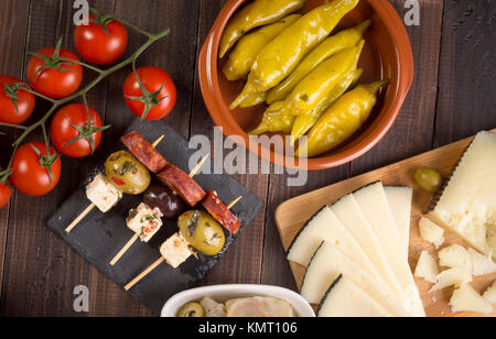 Sharing mixed spanish tapas starters on table. Top view - Stock Photo