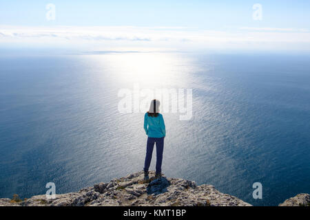 Athletic young woman standing on the rocky top of the mountain against the blue of sky and sea. Back to the camera - Stock Photo